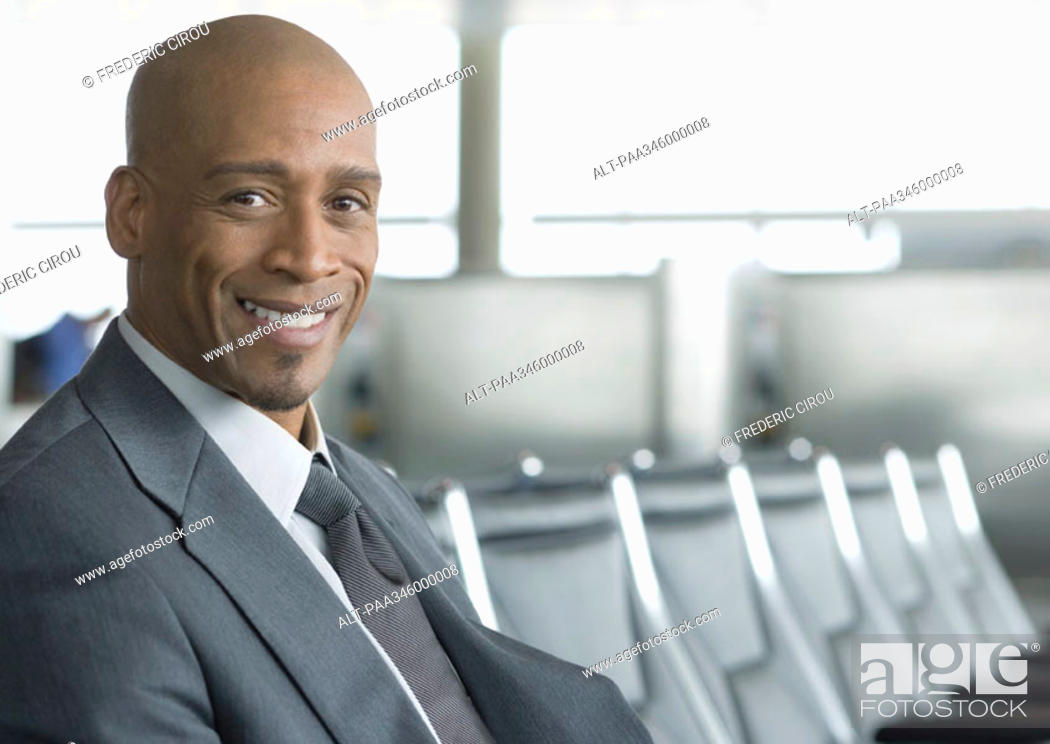 Stock Photo: Businessman sitting in airport lounge, smiling at camera.