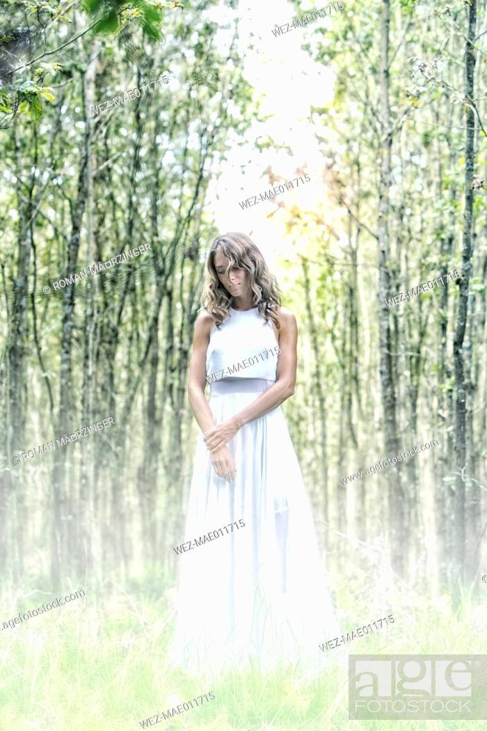 Imagen: Young woman wearing white dress in the forest.