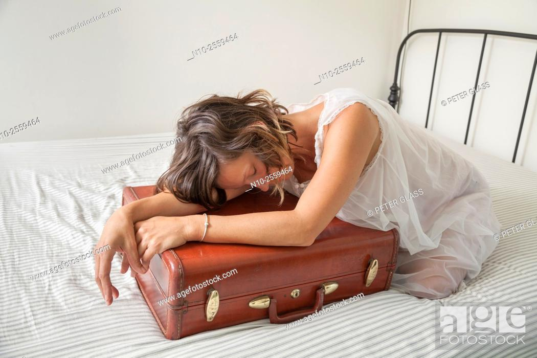Stock Photo: Young woman leaning on her suitcase.