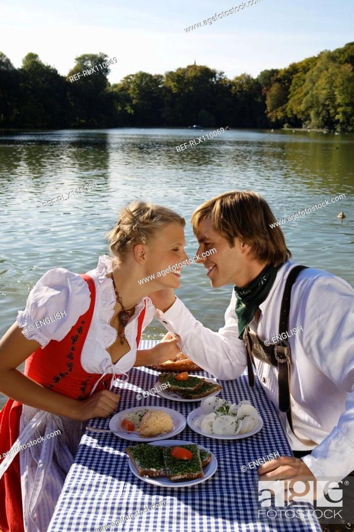 Stock Photo: Young couple in traditional Bavarian outfit, caressing in beer garden, Munich.