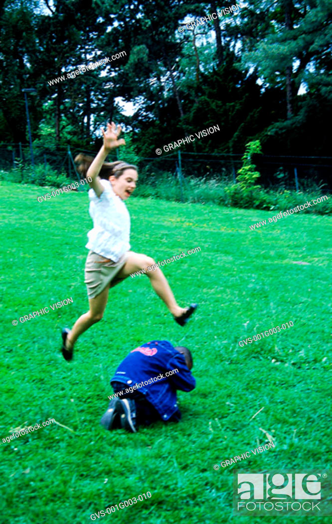 Stock Photo: Young girl jumping over boy.
