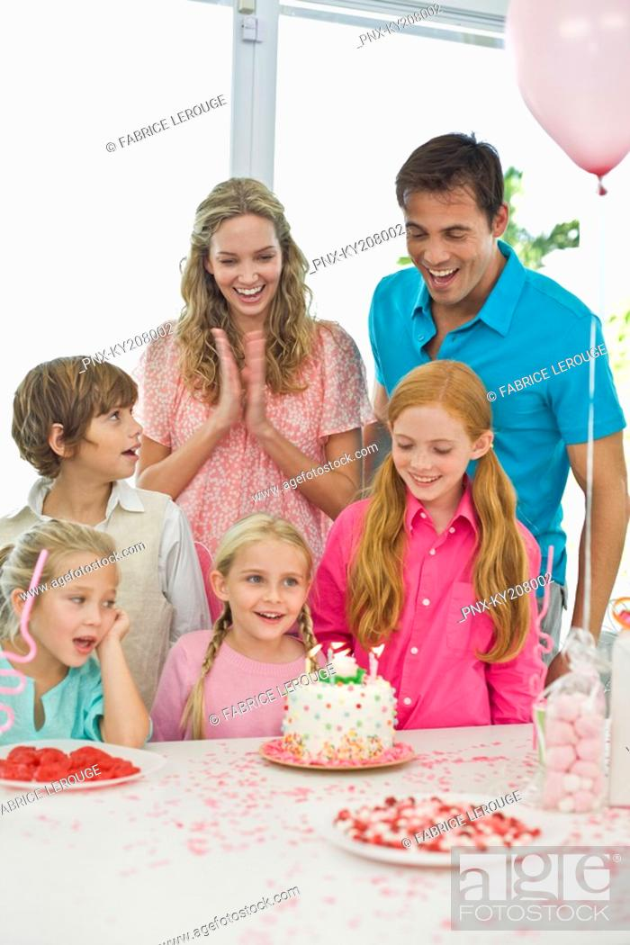 Stock Photo: Girl celebrating her birthday with her parents and friends.