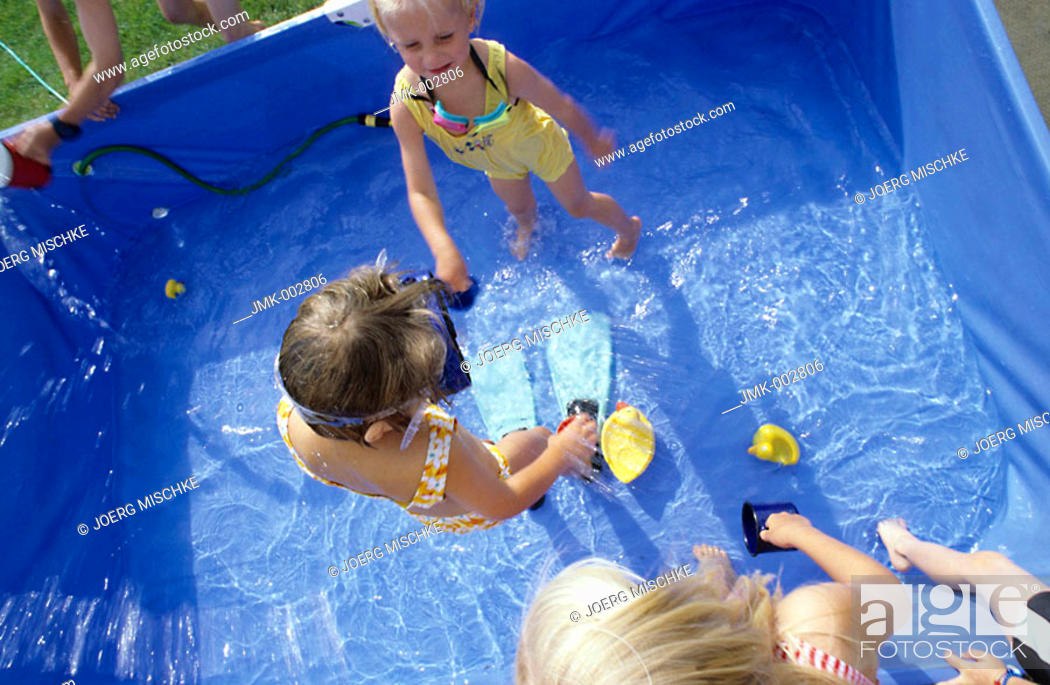 Stock Photo: Three children, girls, 5-10 years old, playing in the garden in a swimming pool in the garden.