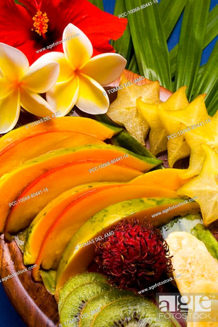 Stock Photo: Studio shot pf a variety of tropical fruit sliced on a platter, with flowers.