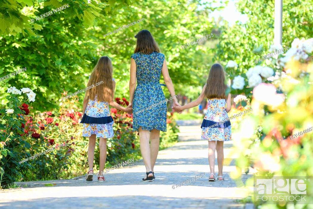 Stock Photo: Mom walks down the path in the flowering garden by the hand with her two daughters back in the frame.