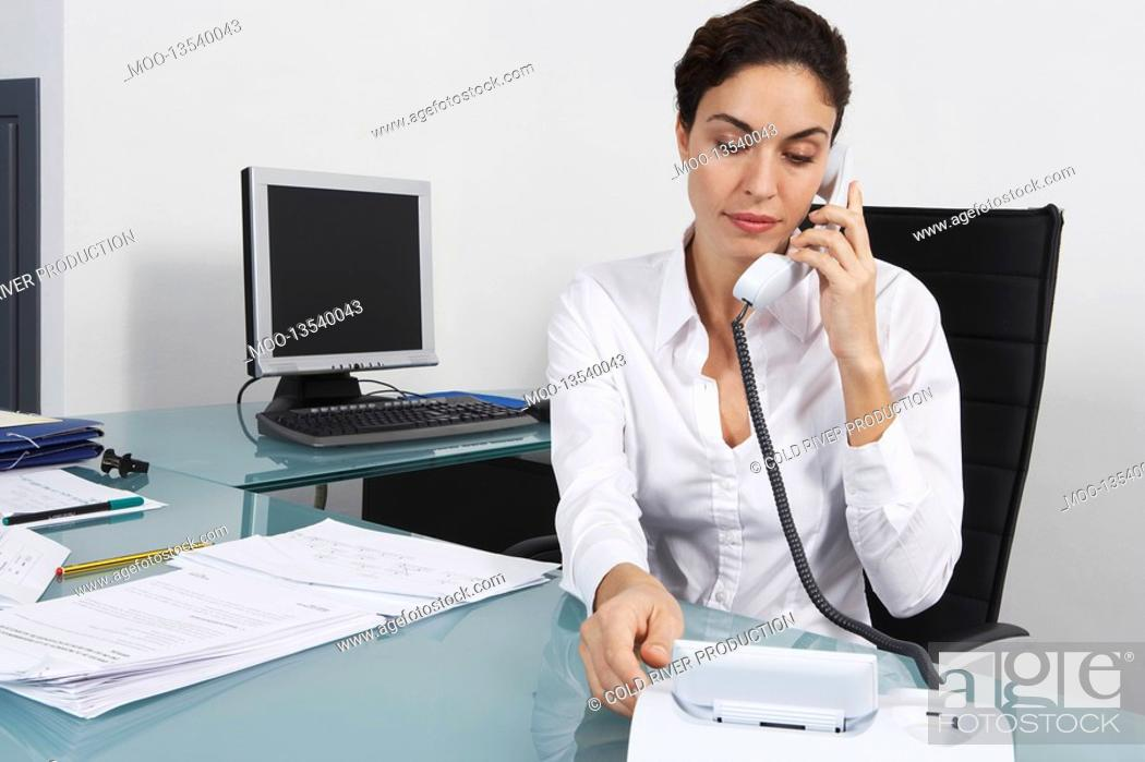 Stock Photo: Businesswoman dialling telephone in office.