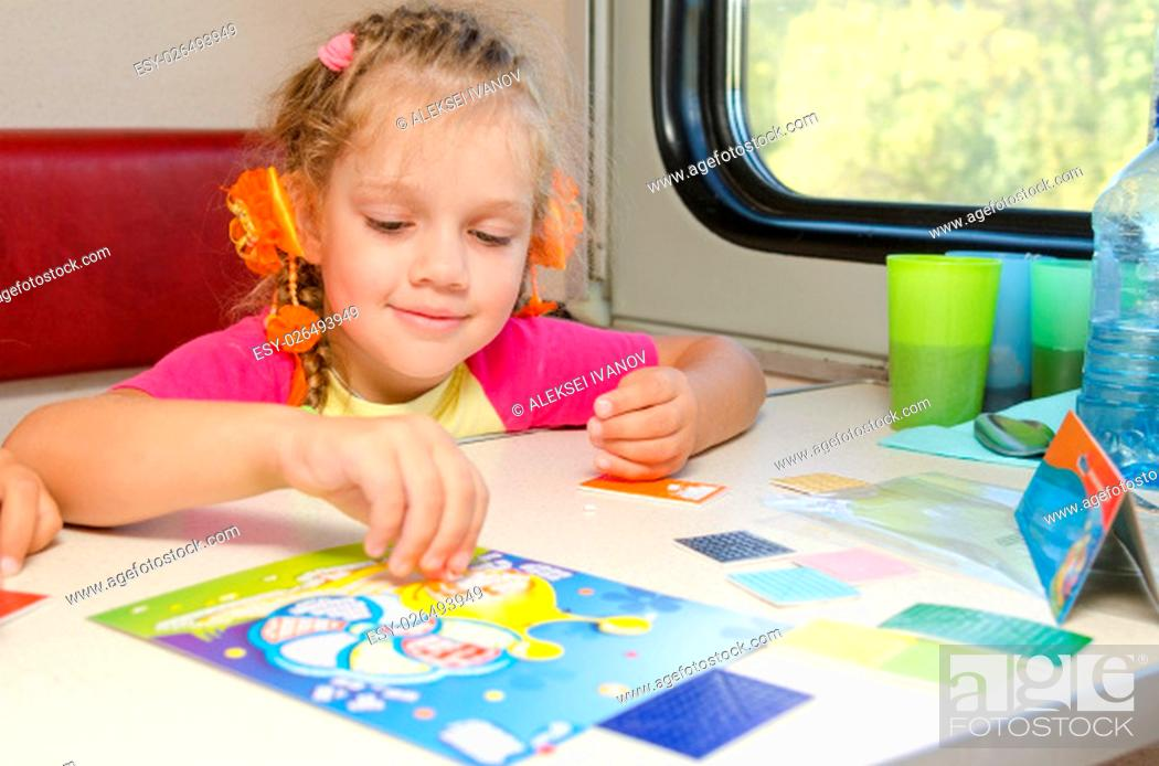 Stock Photo: A small child in a train of fun playing at the table at the lower place in the second-class compartment wagon.