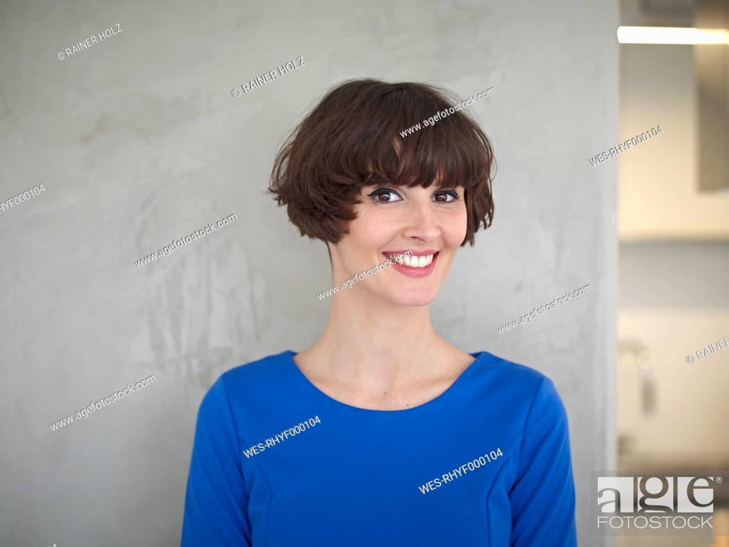 Stock Photo: Germany, Cologne, Young woman in kitchen, smiling, portrait.