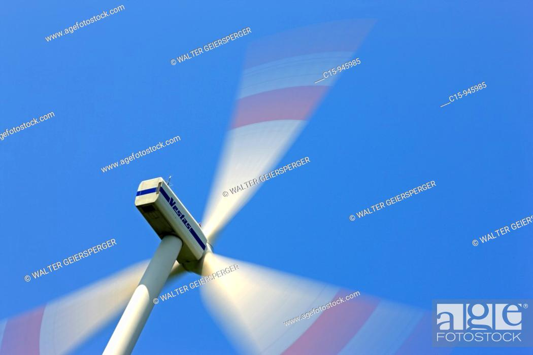 Stock Photo: Spinning Wind turbine generator against blue sky.