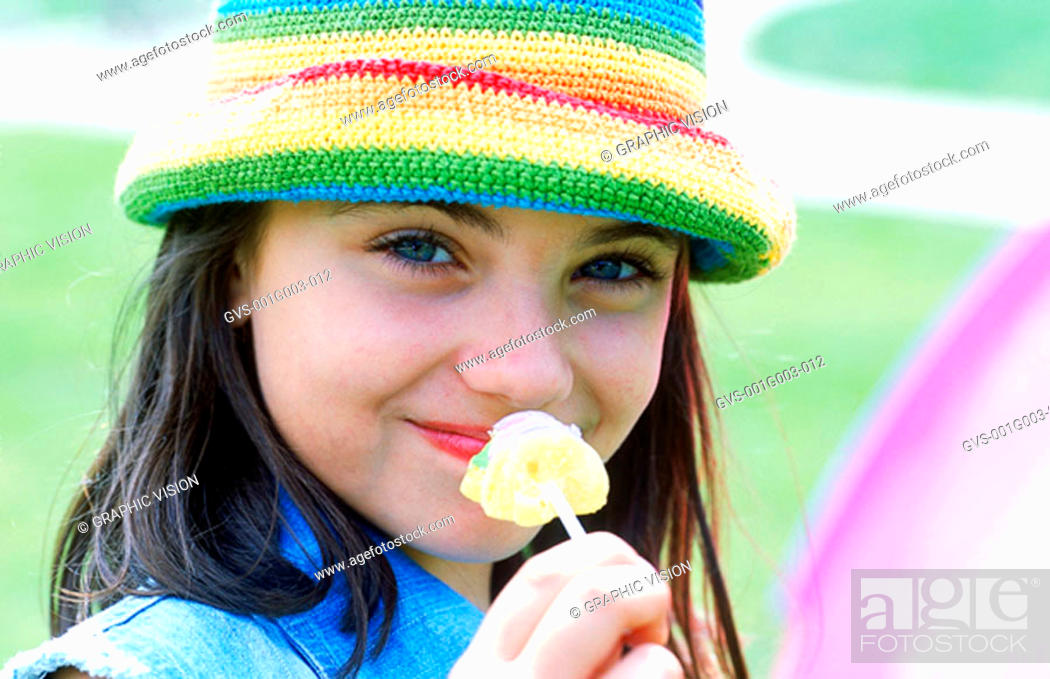 Stock Photo: Young girl holding candy.
