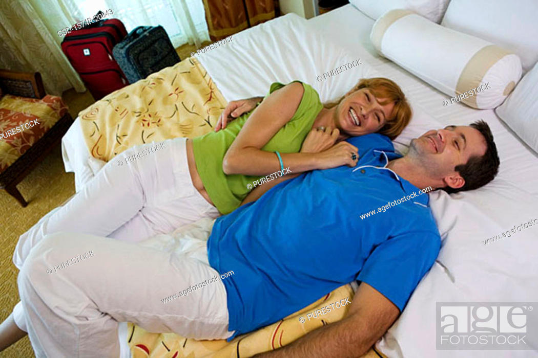 Stock Photo: High angle view of a young couple lying on the bed and smiling.