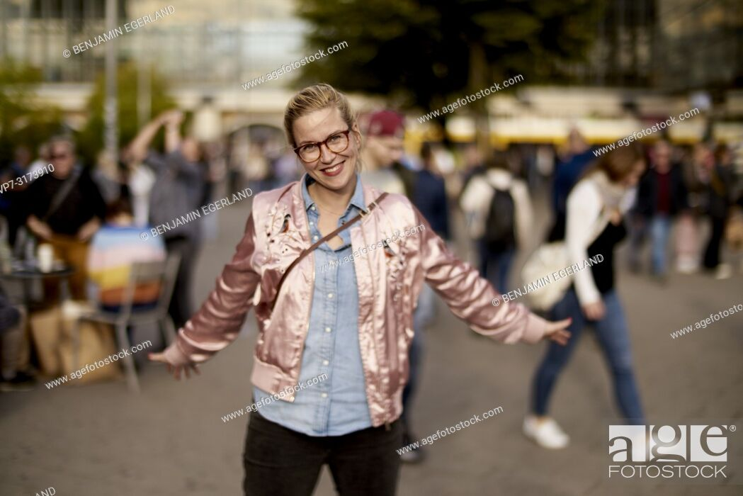 Imagen: Lively woman with open arms dancing at Alexanderplatz, Berlin, Germany.