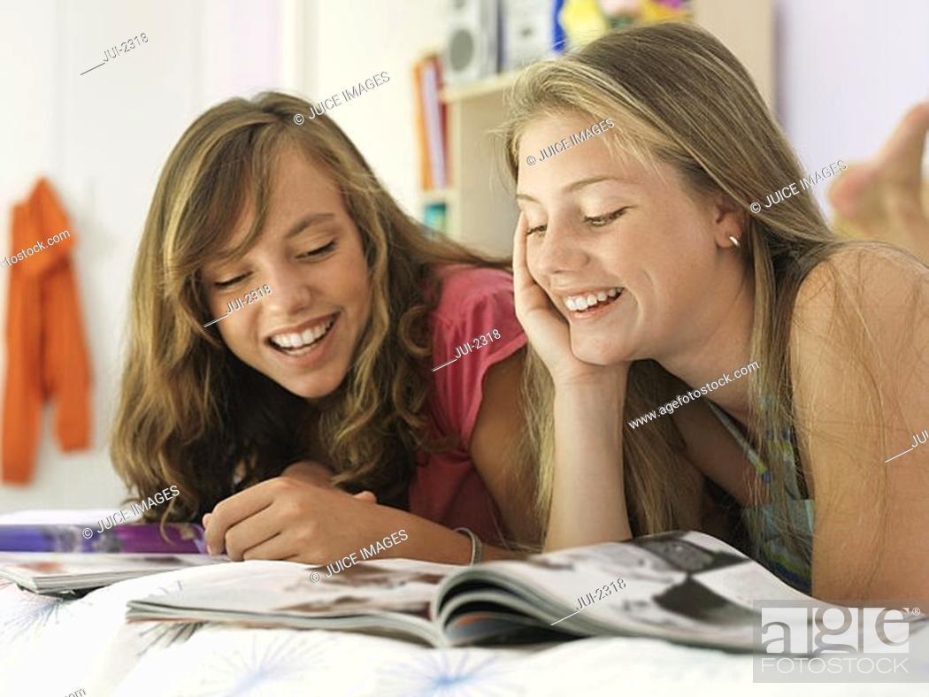 Stock Photo: Two teenage girls 15-17 lying on bed, reading magazine, smiling, close-up.