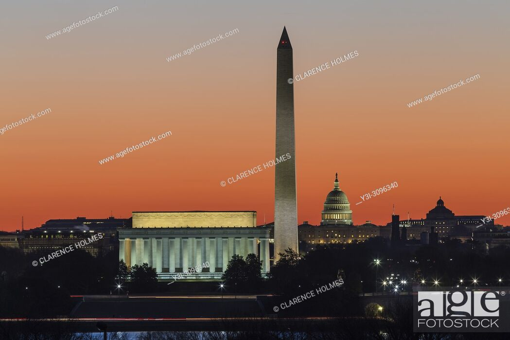 Stock Photo: The Lincoln Memorial, Washington Monument, and US Capitol building set against an orange sky during morning twilight in Washington, DC.