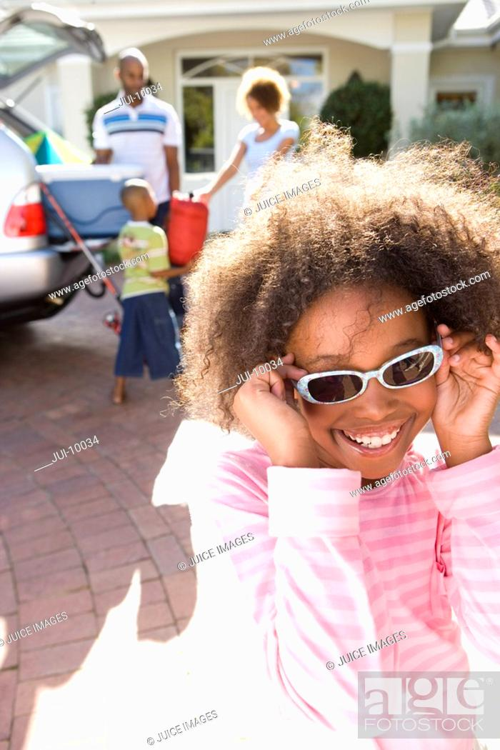 Stock Photo: Girl 8-10 holding sunglasses to face in driveway, smiling.