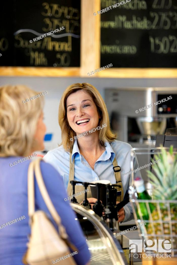 Stock Photo: Server in supermarket talking with customer.