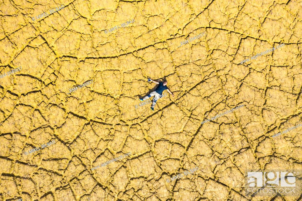 Stock Photo: Man lying on a land cracked by drought. Yesa reservoir area. Zaragoza, Aragon, Spain, Europe.