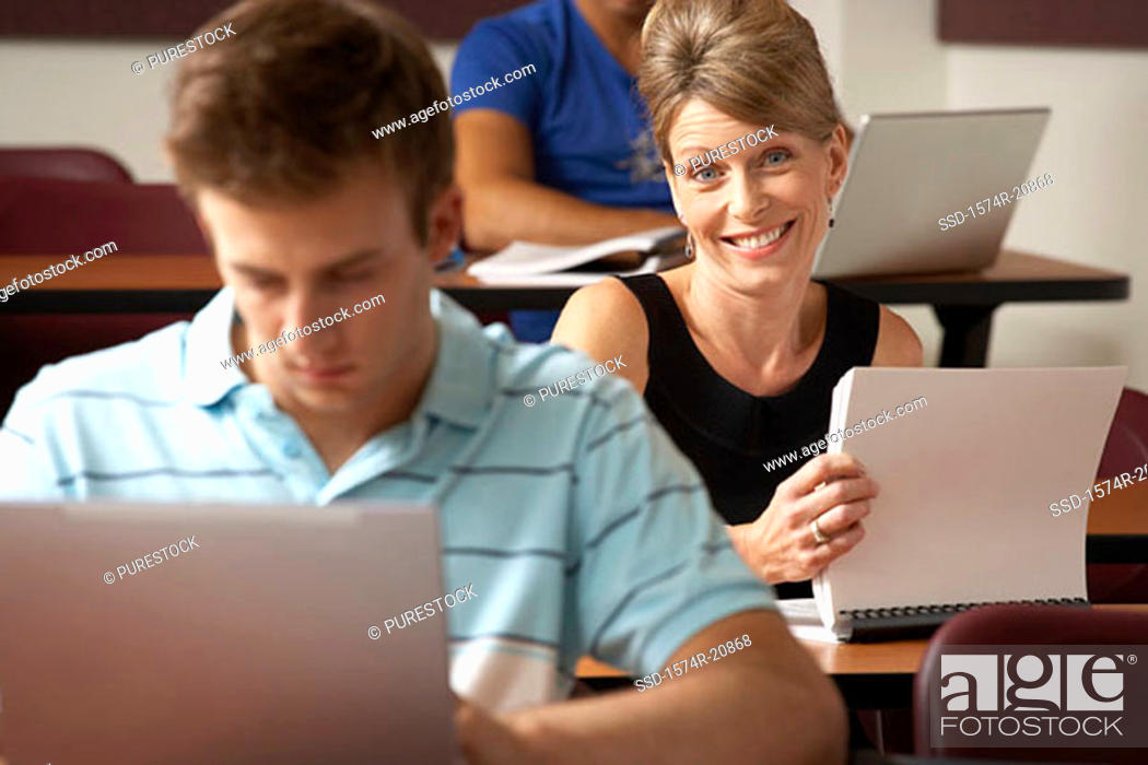 Stock Photo: Portrait of a college student smiling with another student sitting in front of her and using a laptop.