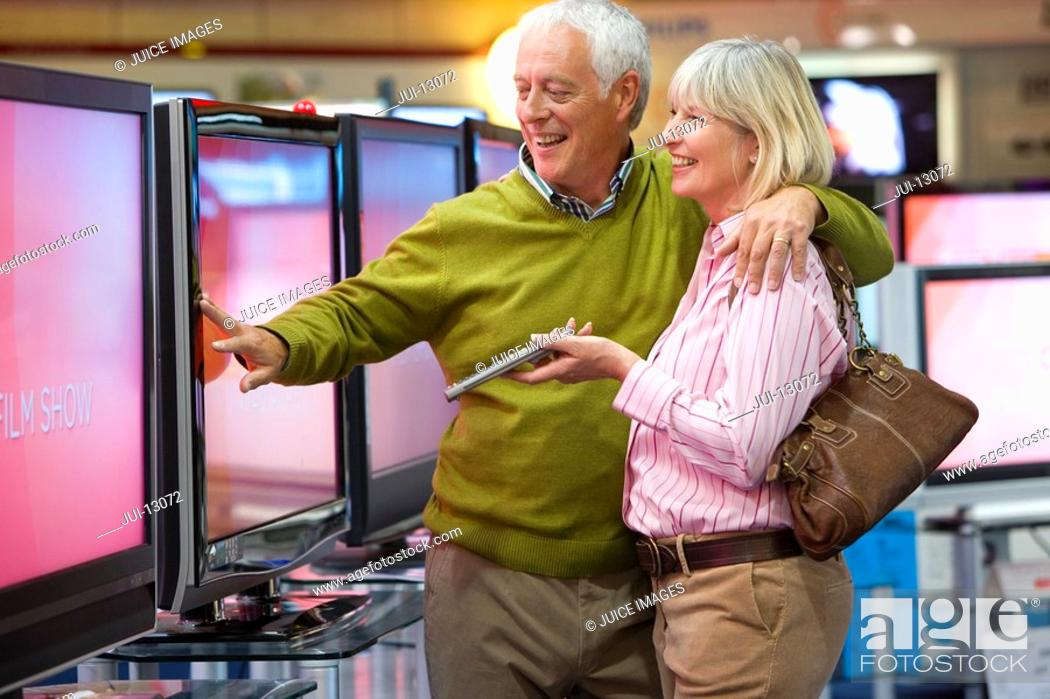 Stock Photo: Mature couple arm in arm shopping for television, smiling.