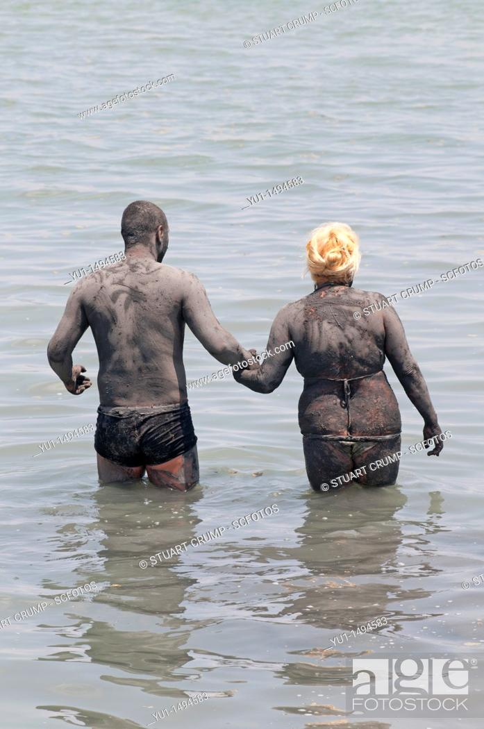Stock Photo: Couple cover themselves in mud from Lo Pagan beach, believed to have beneficial properties for the skin, Lo Pagan, Region of Murcia, South Eastern Spain.