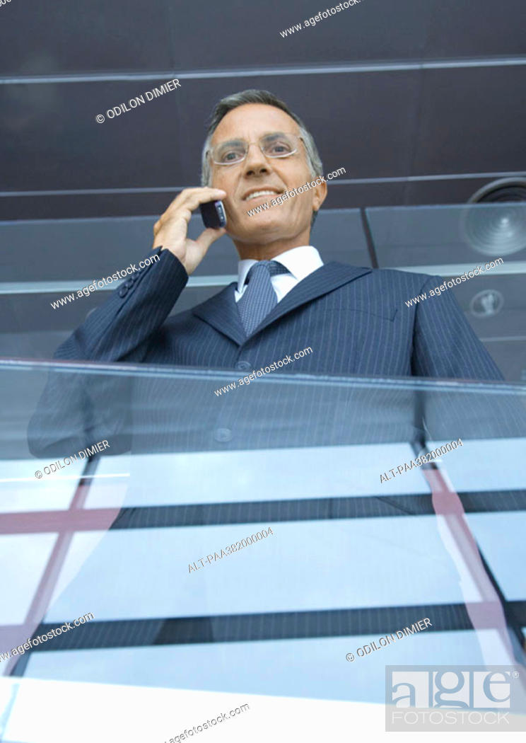 Stock Photo: Businessman using cell phone, low angle view.