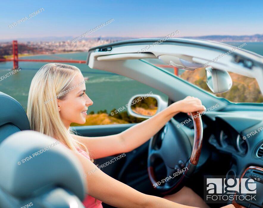 Stock Photo: woman driving convertible car over golden gate.