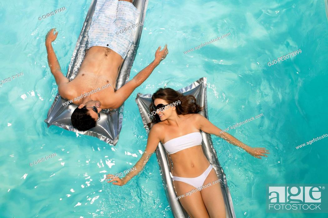 Stock Photo: Couple floating in swimming pool together.