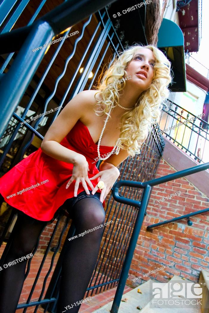 Stock Photo: Blond girl red standing on stairs.