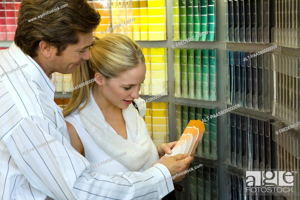 Stock Photo: Couple looking at color swatches in store.