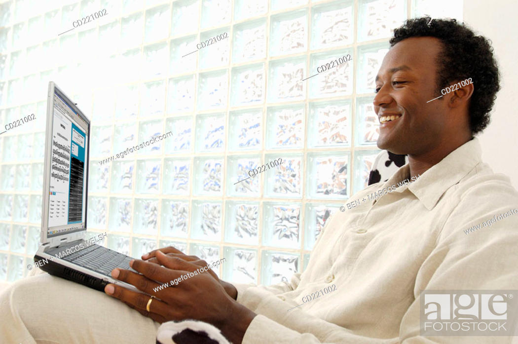 Stock Photo: Black man, in profile, holding computer.
