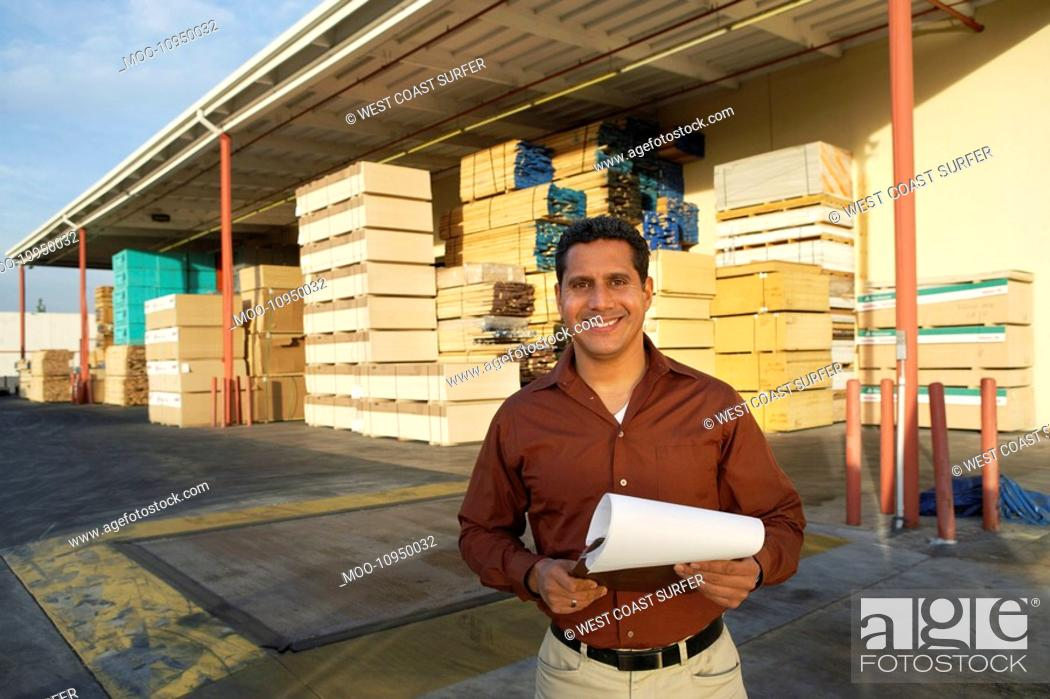 Stock Photo: Man with clipboard outside warehouse full of wood.