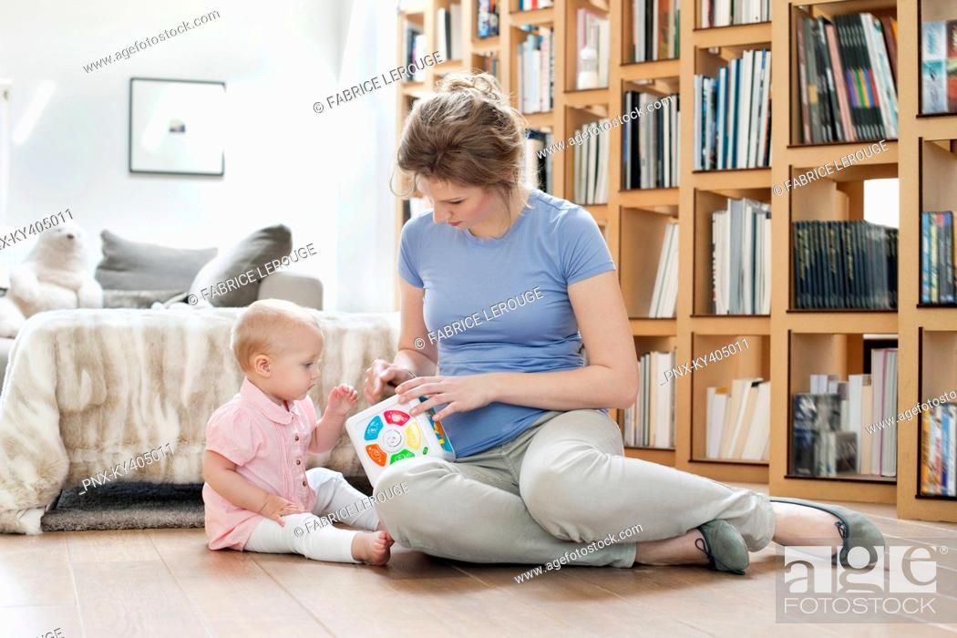 Stock Photo: Woman sitting near her daughter playing with a toy.