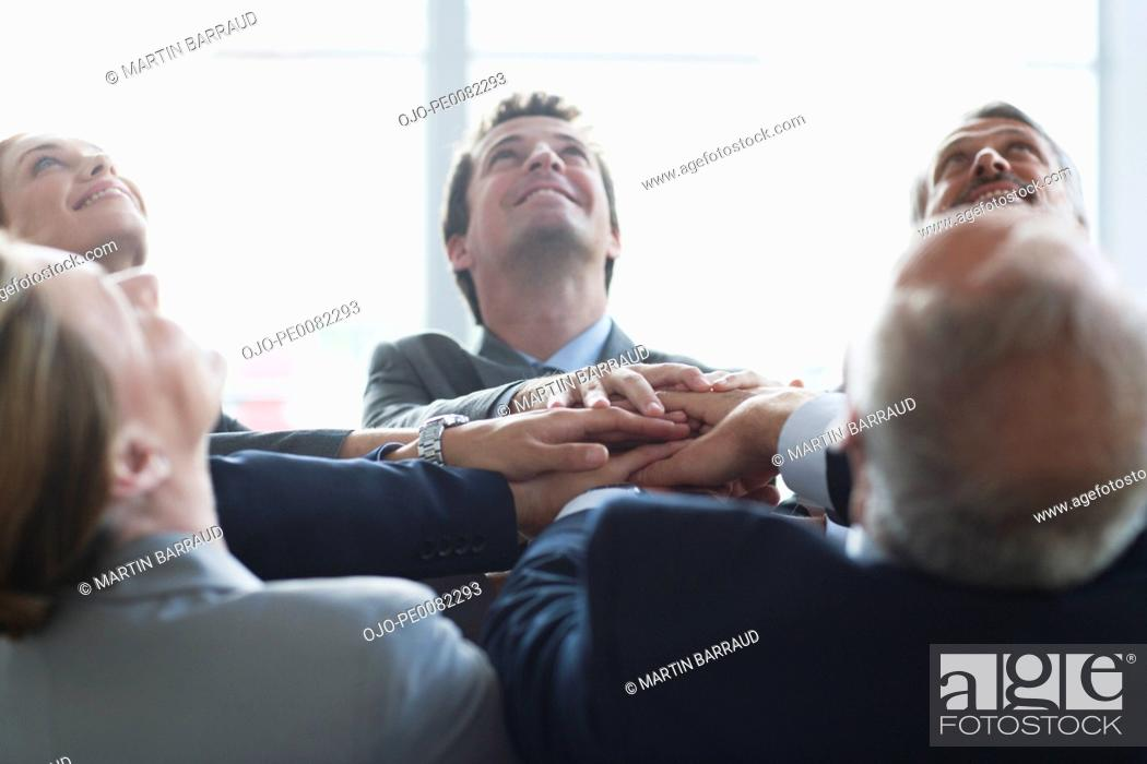 Stock Photo: Business people stacking hands in circle and looking up.
