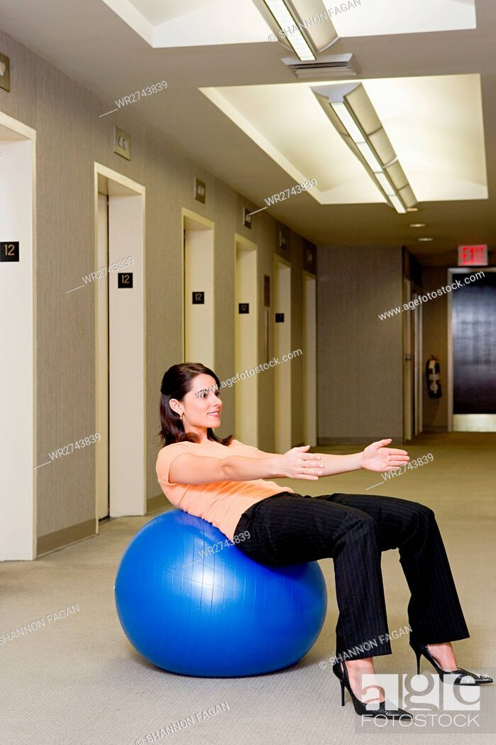 Stock Photo: Female office worker using an exercise ball.