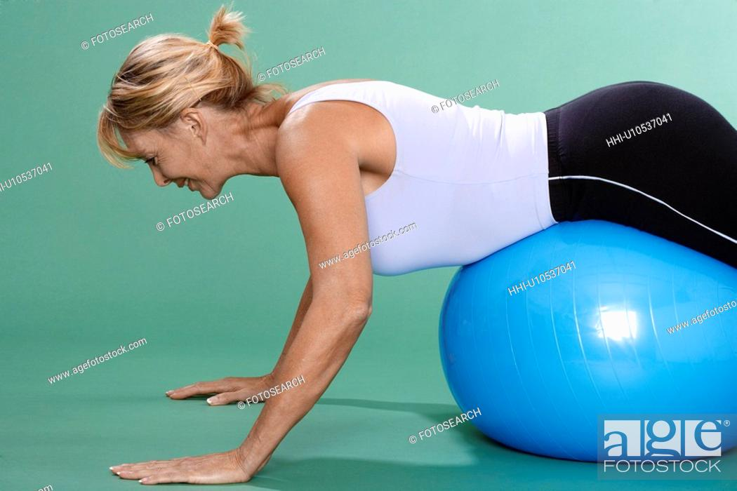 Stock Photo: Mature woman exercising on Swiss ball.