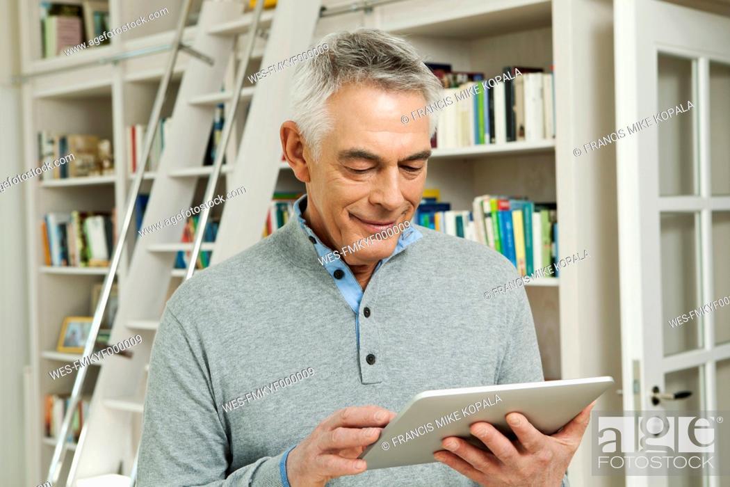Stock Photo: Germany, Berlin, Senior man using tablet pc, smiling.