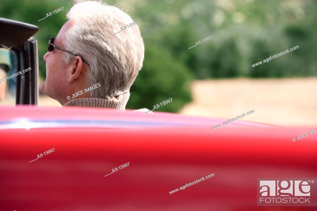Stock Photo: Senior man sitting in red convertible.