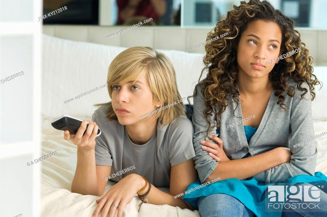 Stock Photo: Teenage boy watching television with a girl sitting beside him.