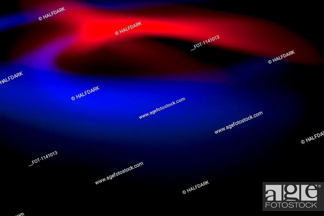 Stock Photo: Abstract patterns of blue and red light on a black background.