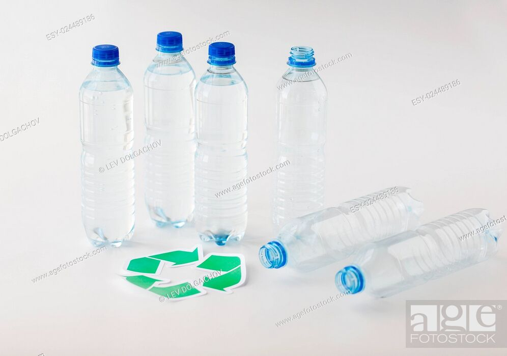 Stock Photo: recycling, reuse, garbage disposal, environment and ecology concept - close up of plastic water bottles with green recycle symbol on table.