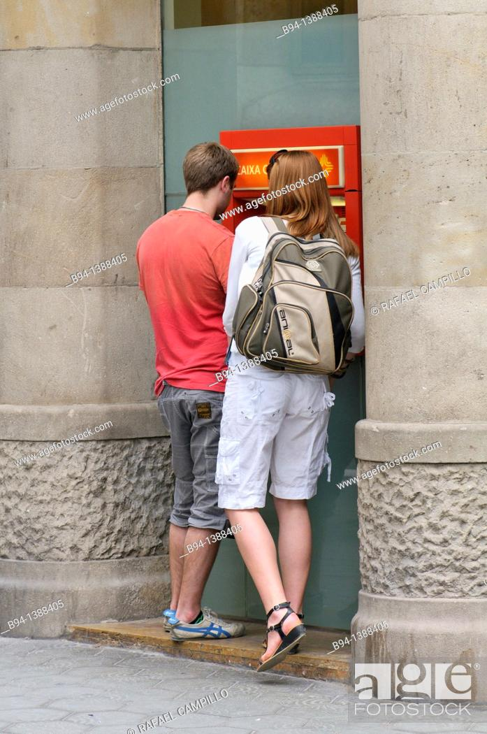 Stock Photo: Couple in an ATM. Barcelona. Catalonia. Spain.
