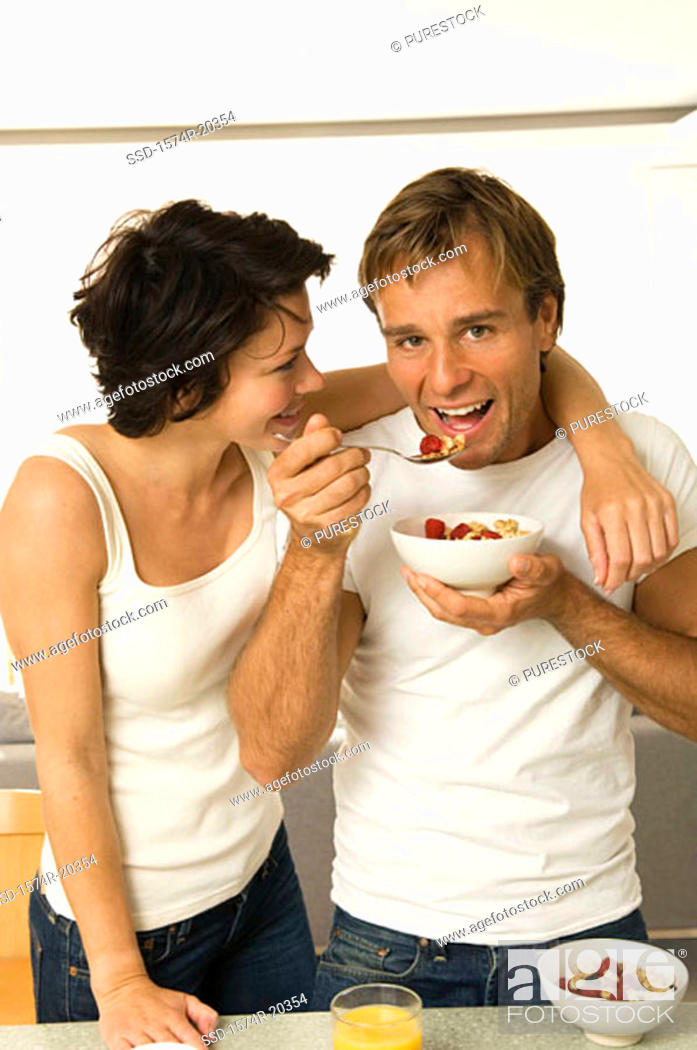 Stock Photo: Portrait of a young man eating fruit salad with a young woman looking at him.