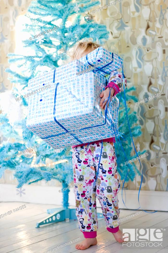 Stock Photo: Child carrying stack of Christmas gifts.