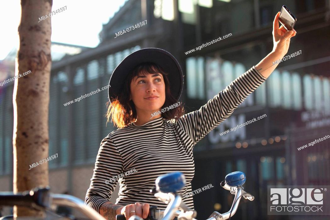 Stock Photo: Young woman by bicycle in Barcelona, Catalonia, Spain.