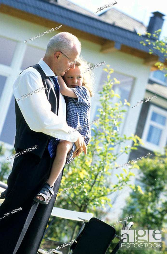 Stock Photo: A senior, businessman, father, grandfather, 45-50 50-55 55-60 years old, holding a little girl, 1-5 5-10 years old, on his arms in a summerly garden.