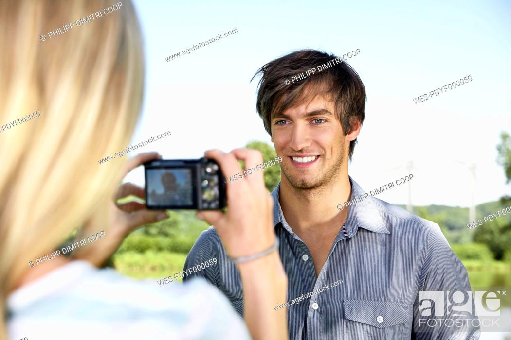 Stock Photo: Germany, Cologne, Young woman taking photo of man.