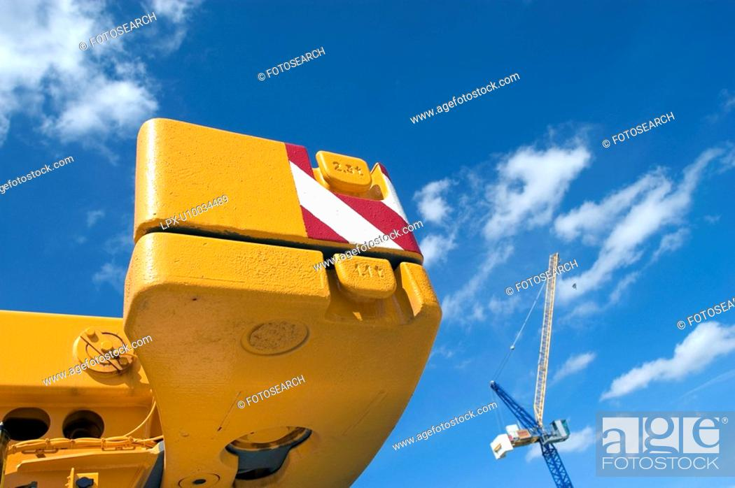 Stock Photo: Detail of mobile crane equipped with safety Hazard Stripes and tower crane in the background.