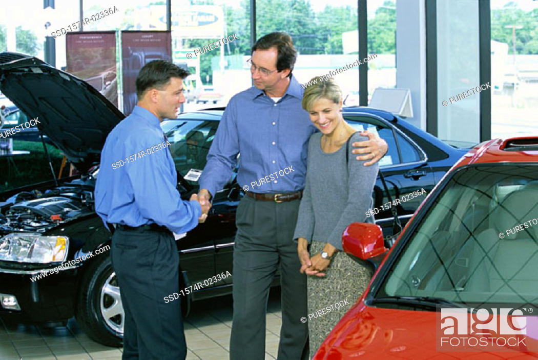 Stock Photo: Mid adult couple talking to a car salesman in a car showroom.