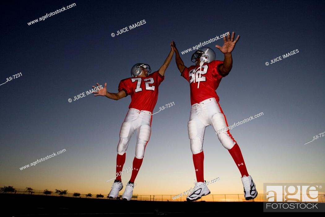 Stock Photo: Two American football players celebrating on pitch at sunset, jumping up, doing high-fives, low angle view backlit.