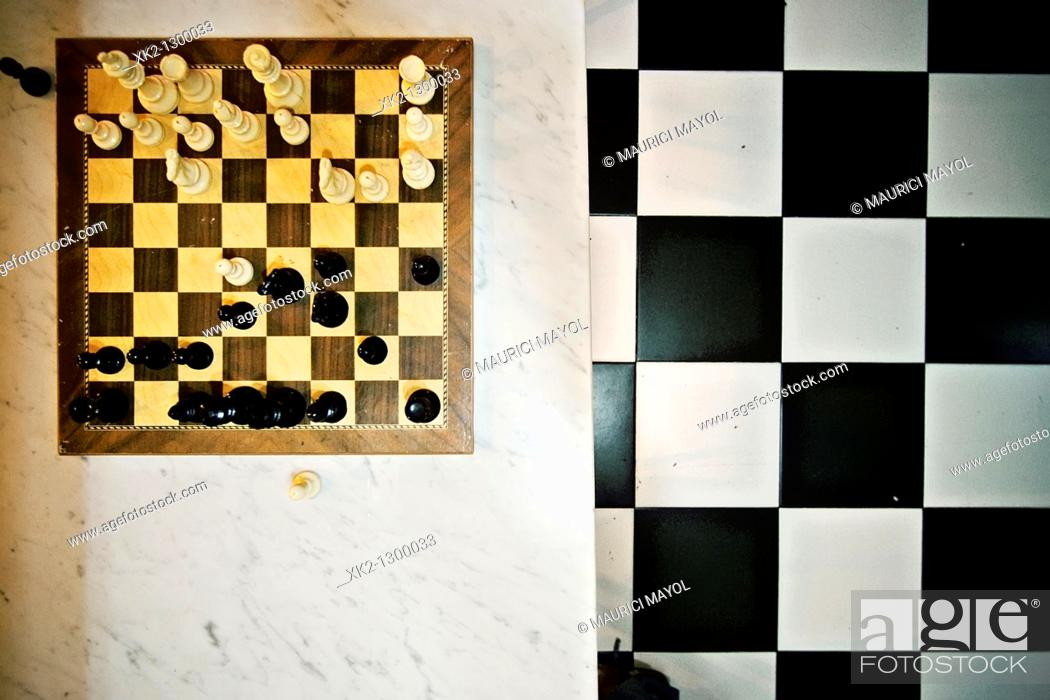 Stock Photo: Chessboard and checkered floor inside a bar.